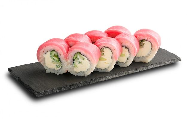 Sushibroodjes met tonijn, komkommer en roomkaas binnen op zwarte die lei op wit wordt geïsoleerd.