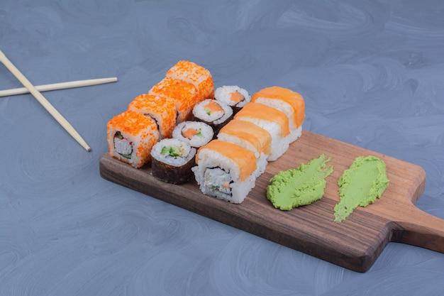 Sushibroodjes met wasabisaus op een houten schotel