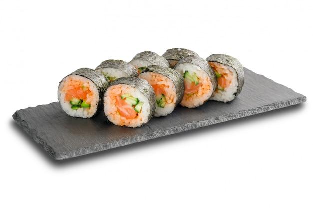 Sushibroodjes met zalm en komkommer in noriblad worden verpakt op zwarte lei of steenschalieoppervlakte op wit wordt geïsoleerd dat