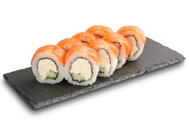 Sushibroodjes met zalm, komkommer, noriblad en roomkaas binnen op zwarte leisteen of stenen schalie geïsoleerd oppervlak