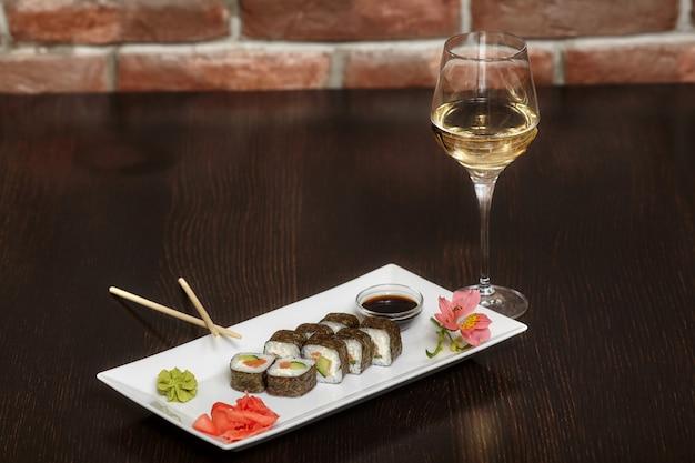 Sushibroodjes op witte plaat en glas wijn