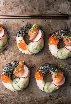 Sushidoughnuts met zalm, komkommer en radijs op donkere oppervlaktebovenaanzicht. hybride voedingsmiddelen.