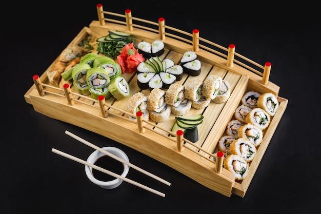 Sushilijst met de broodjes van californië, avocado, hosomaki en tempura op een houten lijst