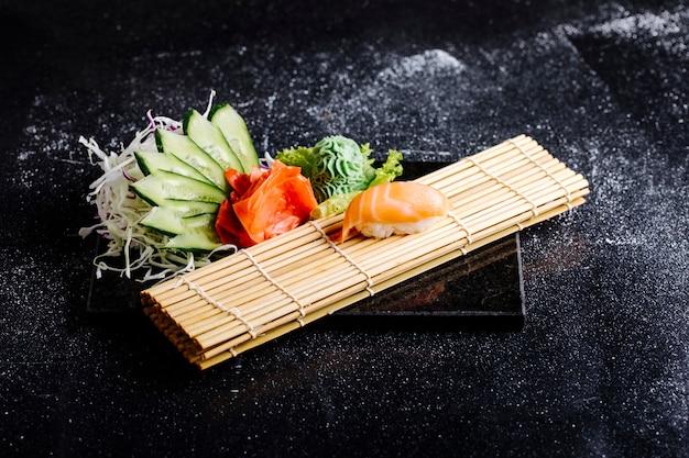 Sushimat, zalmrolletje, wasabi, rode gemarineerde gember en plakjes komkommer.
