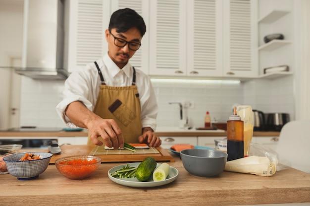 Sushimeester bereidt broodjes op keukenvooraanzicht portret van aziatische chef-kok die thuis kookt