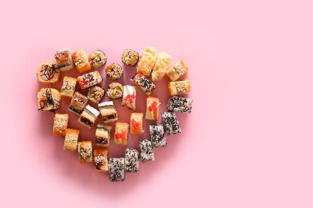 Sushireeks en broodjes dienden als hart op roze. valentijnsdag eten. uitzicht van boven. kopieer ruimte. levering op feestdagen.