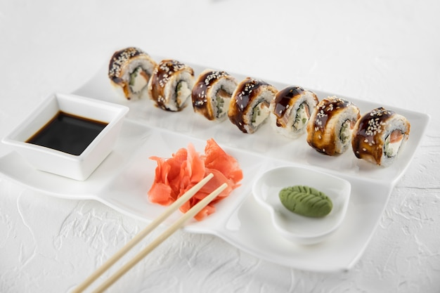 Sushirolletjes gekookt met paling, zalm, kaas, komkommer, geserveerd op het witte grote bord, bordjes met wasabi, sojasaus, gember en bamboestokken, traditioneel japans eten