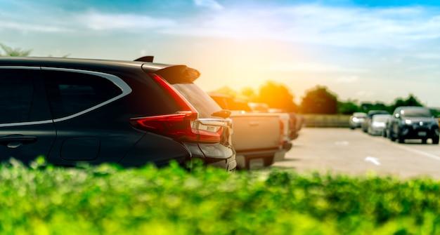 Suv-auto op concreet parkeerterrein bij fabriek dichtbij het overzees met blauwe hemel en wolken wordt geparkeerd die.