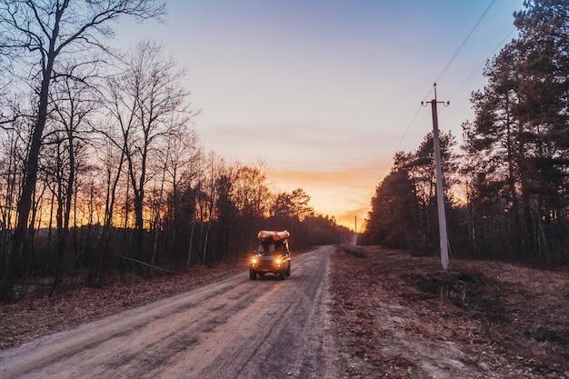 Suv rijdt op een onverharde weg in de avond