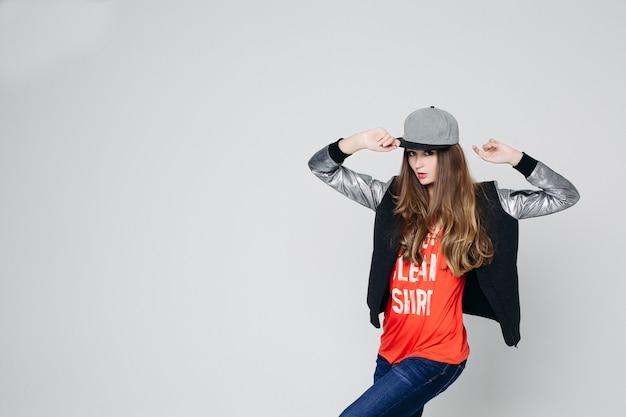 Swag stijlvolle tienermeisje in cap poseren met handen omhoog.