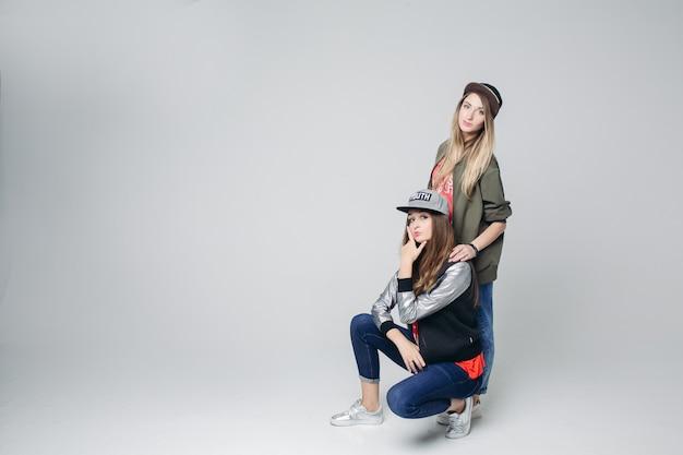Swag-vriendinnen hipster in stijlvolle slijtage en petten op het hoofd.