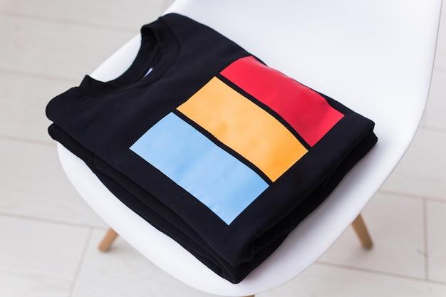 Sweatshirts en hoodies liggen op een stoel in de winkel