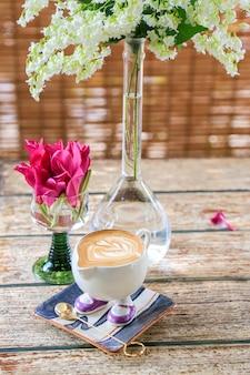Sweet tabel met bloemen en een kop warme latte op een houten tafel