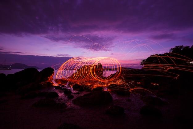 Swing fire swirl staalwol lichte fotografie over de steen met reflex in het water