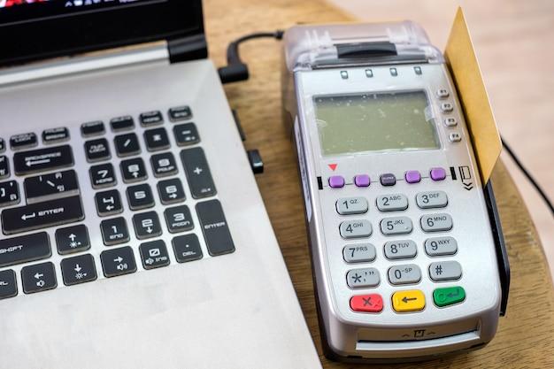 Swipe creditcard gebruiken op betaalterminal met laptop op houten tafel