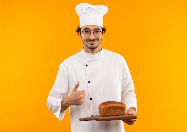 Swmiling jonge mannelijke kok die eenvormige chef-kok en glazen draagt die brood op scherpe raad houden zijn duim omhoog geïsoleerd op gele muur