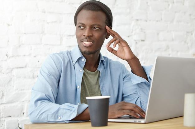 Sylish african american college student met koffie tijdens de lunch in de cafetaria, met behulp van laptop tijdens het werken aan diplomaproject of voorbereiden op lessen. jonge zwarte hipster genieten van ontbijt in café