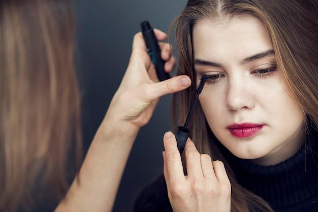Sylist die mascara op model toepast