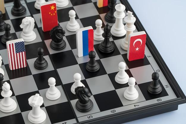 Symbolen van de vlaggen van de wereld op het schaakbord. het concept van politiek spel.