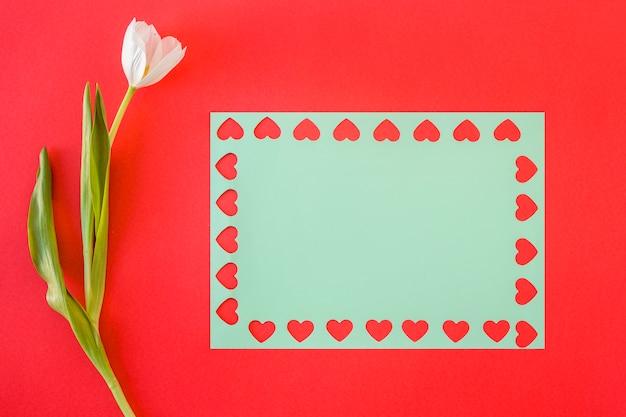 Symbolen van hart op blauw papier in de buurt van bloem