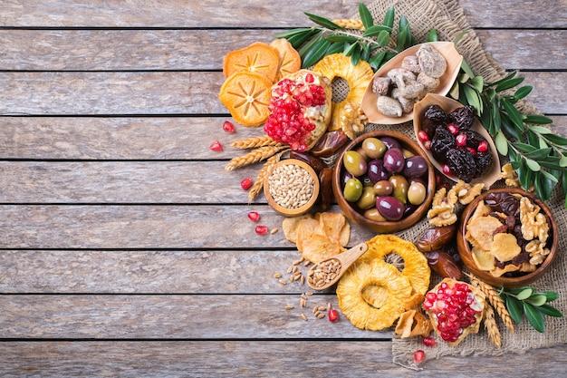 Symbolen van judaic vakantie tu bishvat, rosh hashana nieuwjaar van de bomen. mix van gedroogde vruchten, dadels, vijgen, druif, gerst, tarwe, olijven, granaatappel op een houten tafel. kopieer de ruimte plat lag achtergrond