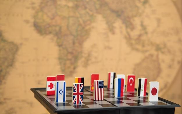 Symbolen van landen op het schaakbord tegen tegen de achtergrond de politieke kaart van de wereld