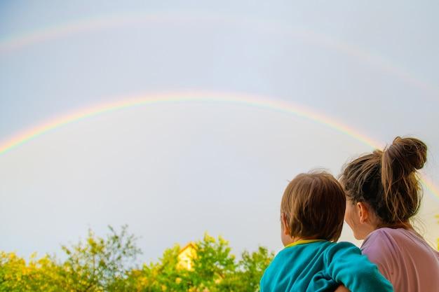 Symboliek van liefde, regenbooghemel, liefde. hartvormige handen en regenboog aan de hemel. dubbele regenboog.
