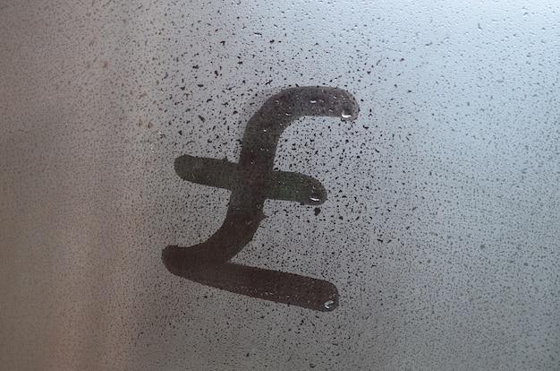 Symbool van engelse ponden wordt geschreven met een vinger op het oppervlak van het beslagen glas