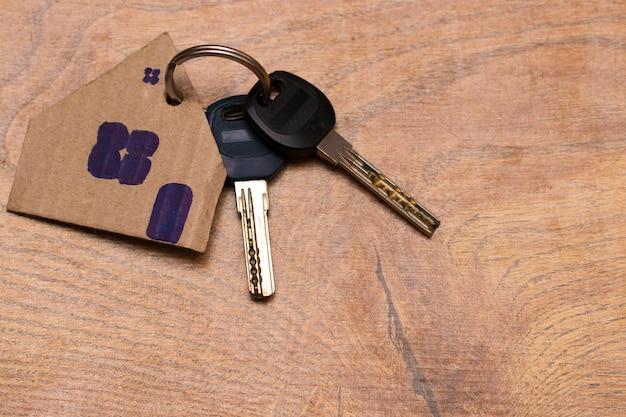Symbool van het huis met sleutel op houten achtergrond.