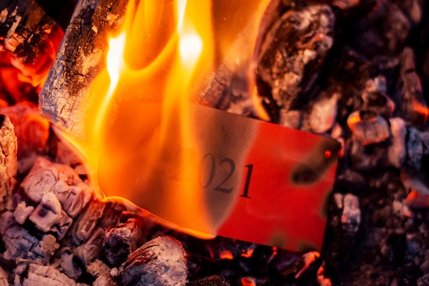 Symbool van het jaar 2021, dat in vlammen brandt. close-up foto van fel oranje vuur, verbrande as en rood vel papier erin.