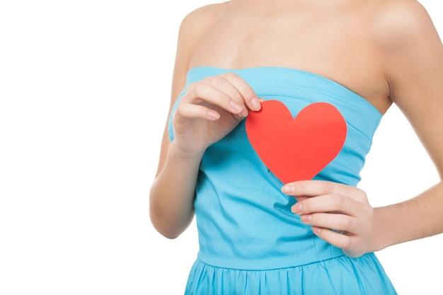 Symbool van liefde. bijgesneden afbeelding van een jonge vrouw die een papieren hart vasthoudt terwijl ze op een witte achtergrond staat