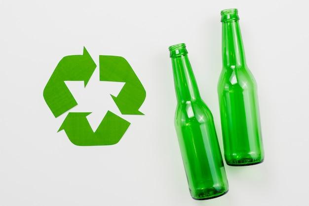Symbool van recycling naast glazen flessen