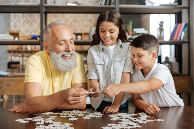 Symbool van saamhorigheid. hechte pre-tiener broers en zussen die samen met hun vrolijke grootvader een legpuzzel in elkaar zetten en drie stukjes samenvoegen