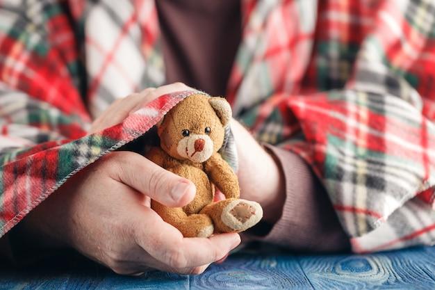 Symbool van zorg, mannelijke hand houden beer speelgoed