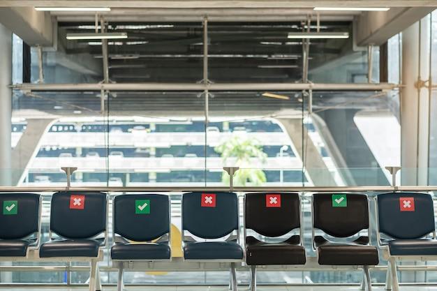 Symboolsticker op stoel in internationale luchthaven. nieuwe normale en sociale afstandsconcepten, bescherming coronavirusziekte (covid-19) infectie