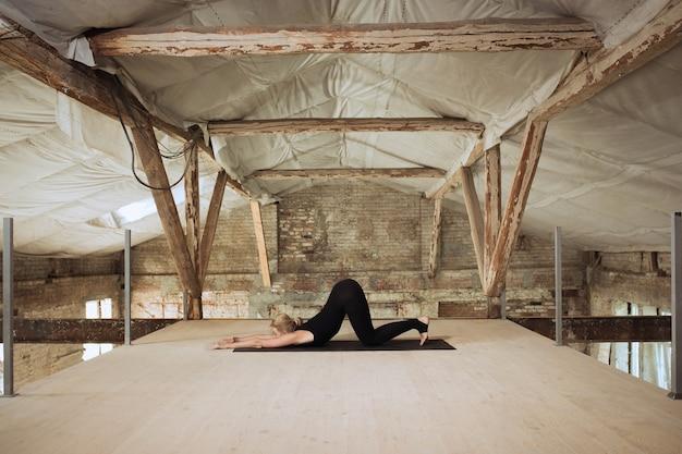 Symmetrie. een jonge atletische vrouw oefent yoga op een verlaten bouwgebouw. geestelijke en lichamelijke gezondheid. concept van een gezonde levensstijl, sport, activiteit, gewichtsverlies, concentratie.