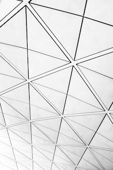 Symmetrisch driehoekspatroon op vensters met uitzicht op een grijze bewolkte hemel