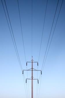 Symmetrische elektrische lijnen mast kabels blauwe hemel