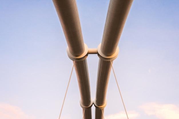 Symmetrische stalen buizen die een hangbrug over een rivier ondersteunen.