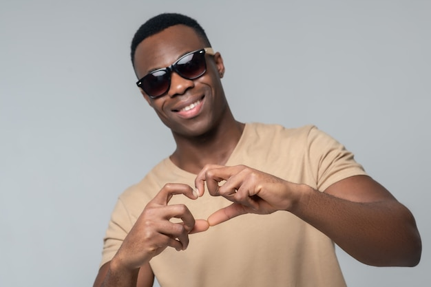 Sympathie. de gelukkige glimlachende donkere gevilde mens in zonnebril die hartteken toont met dient studiofoto in