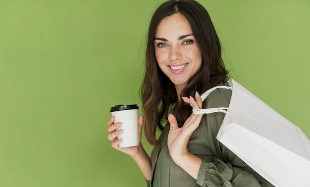 Sympathieke vrouw die op groene achtergrond aan de camera glimlacht