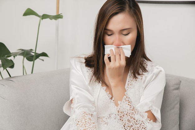 Symptomen van allergische rhinitis bij vrouwen zieke vrouw in witte nachtkleding met een verkoudheid die thuis haar neus in een papieren zakdoekje blaast allergieën voor koud weer