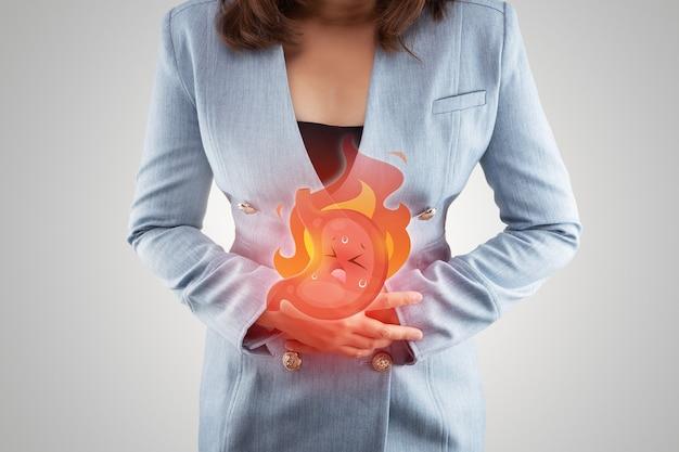 Symptomen van zure refluxziekte of brandend maagzuur, illustratie maagverbranding op het lichaam van de vrouw tegen grijze achtergrond, concept met gezondheidszorg en medicijnen