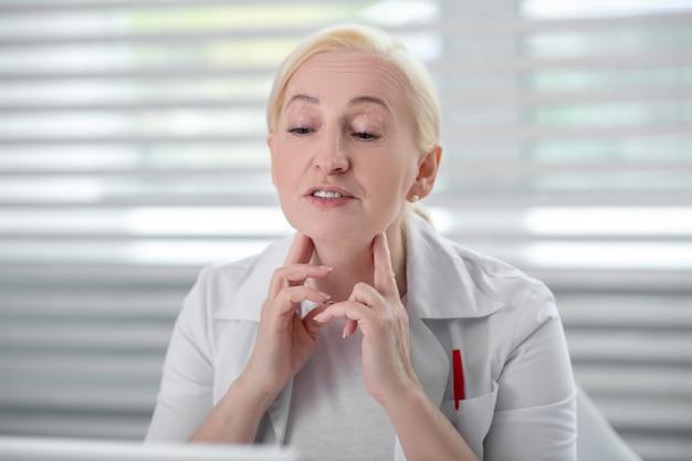 Symptomen. volwassen blonde vrouw arts met handen wat betreft hals die de monitor bekijken, aandachtig spreken, geconcentreerd.