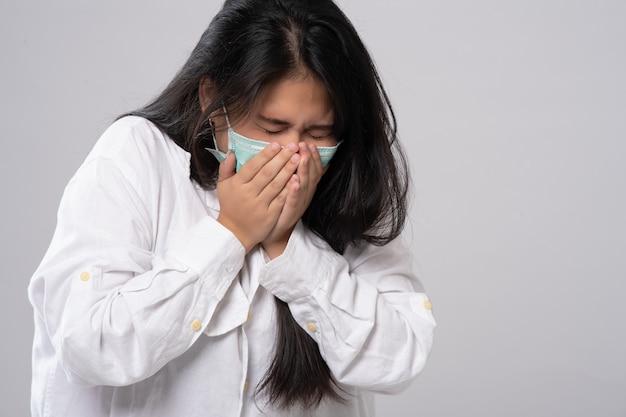 Symptoom van verkoudheid of allergie. zieke jonge aziatische vrouw niezen in masker isoleren op grijs.
