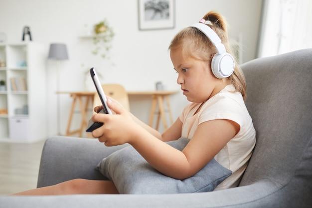 Syndroom van down meisje in draadloze koptelefoon met behulp van digitale tablet tijdens het rusten op fauteuil in de woonkamer