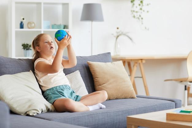 Syndroom van down meisje speelt met model van de planeet terwijl u thuis zit