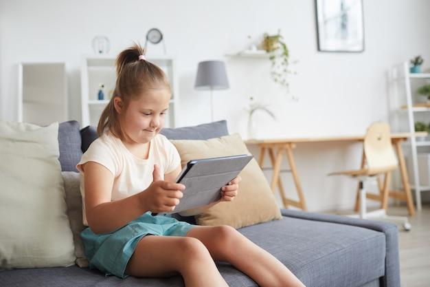 Syndroom van down meisje zittend op de bank en lezen van een boek op digitale tablet in de kamer thuis