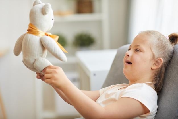 Syndroom van down meisje zittend op een stoel en spelen met speelgoed beer thuis