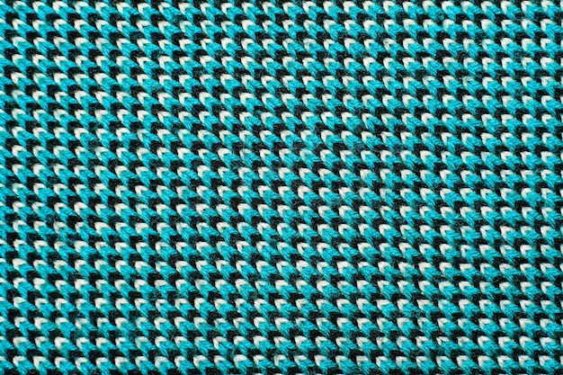 Synthetische gebreide stof met patroonelementen van blauwe, zwarte en witte garens van dichtbij. multicolor patroon gebreide stof textuur. achtergrond